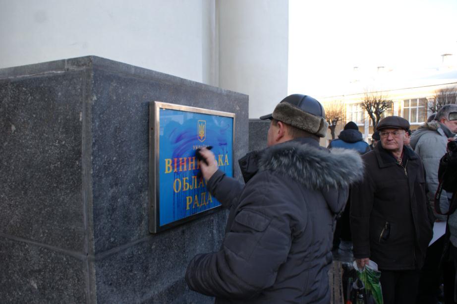 Під час мітингу молодик обіляв таблички Обладержадміністрації червоною рідиною
