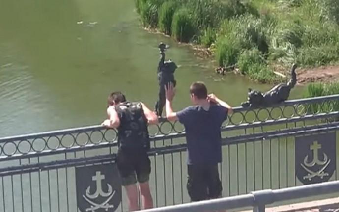 Два молодики розхитували металеві фігурки на Київському мосту (Відео)